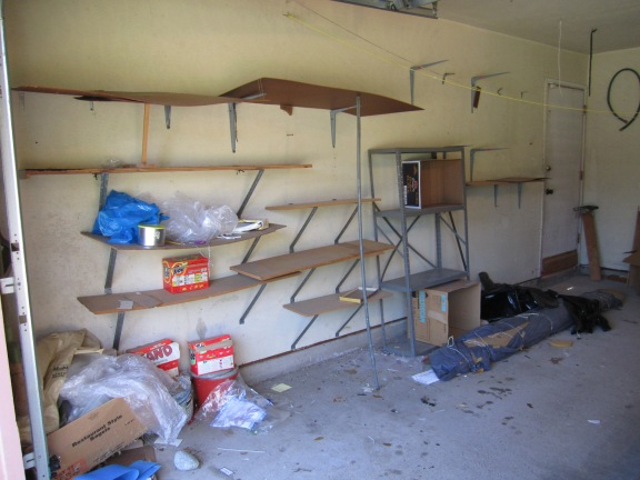 rickety shelves & trash left in the garage, including a roll of carpet!